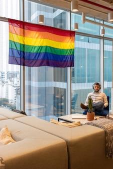 Przystojny mężczyzna w swobodnym stroju, kontemplujący flagę reprezentującą społeczność lgbt