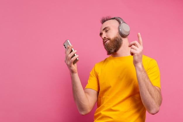 Przystojny mężczyzna w swobodnym tańcu z telefonem komórkowym i słuchawkami na białym tle na różowym tle