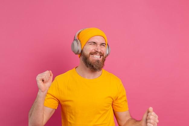 Przystojny mężczyzna w swobodnym tańcu ze słuchawkami na białym tle na różowym tle