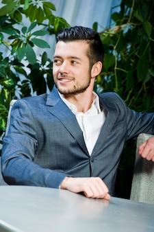 Przystojny mężczyzna w szarym garniturze. portret młodego biznesmena we wnętrzu. portret młodego biznesmena sukcesu.