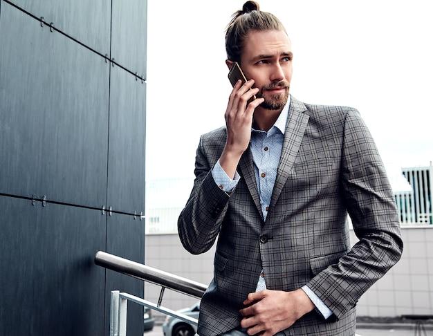 Przystojny mężczyzna w szarym garniturze w kratkę, mówiąc z smartphone