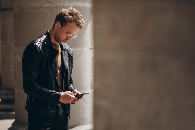Przystojny mężczyzna w widowiskach używać telefon
