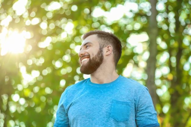 Przystojny mężczyzna w zielonym parku