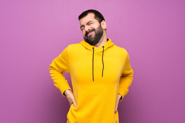 Przystojny mężczyzna w żółtej bluzie cierpiący na bóle pleców za to, że podjął wysiłek