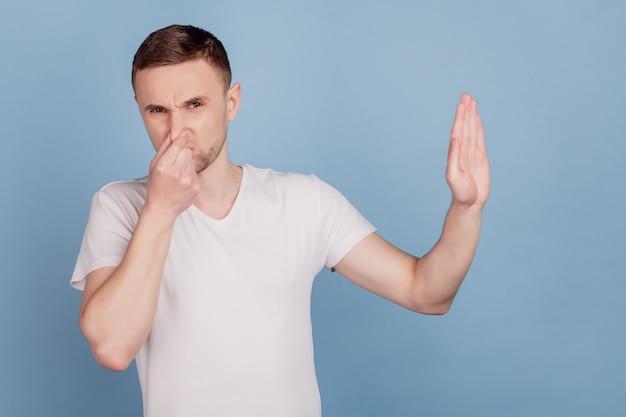 Przystojny mężczyzna wąchający coś śmierdzącego i obrzydliwego, wstrzymujący oddech palcami na nosie izolowanym na niebieskim tle