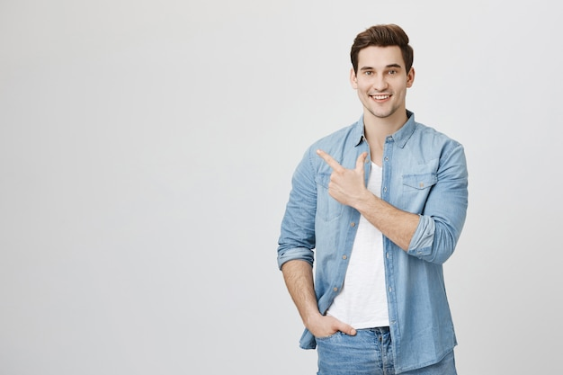 Przystojny mężczyzna, wskazując w lewo i uśmiechnięty