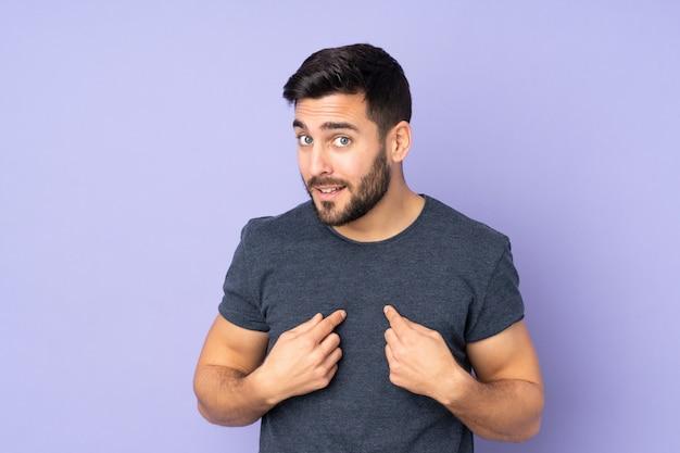 Przystojny mężczyzna wskazuje ja nad odosobnioną purpury ścianą