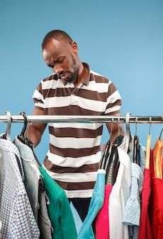 Przystojny mężczyzna wybiera koszula w sklepie z brodą