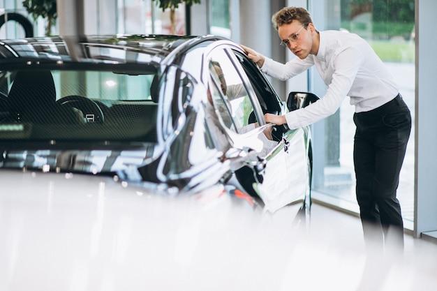 Przystojny mężczyzna wybiera samochód w pokoju pokazowym
