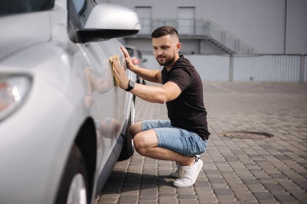 Przystojny mężczyzna wyciera samochód szmatą w salonie w samoobsługowej myjni szarej samochodowej