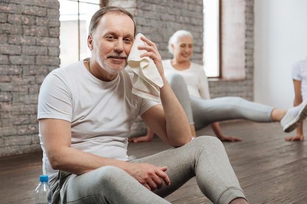 Przystojny mężczyzna wycierając twarz ręcznikiem, kładąc ręce na nogach siedząc na podłodze