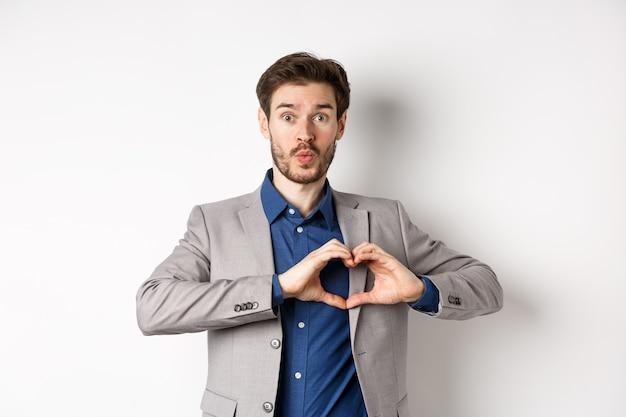 Przystojny mężczyzna wyglądający głupio, pokazując miłość serca, znak i zmarszczone usta, czekając na pocałunek od kochanka, stojąc w garniturze na białym tle.