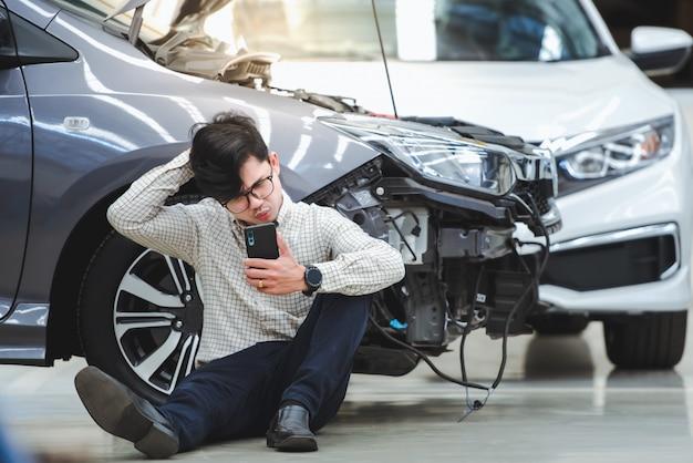 Przystojny mężczyzna wykonał stresujący gest po tym, jak uszkodzony samochód został potrącony przez wypadek, i użył swojego telefonu, aby poprosić o pomoc po tym, jak samochód wyjechał na drogę - samochód ma ubezpieczenie wypadkowe.