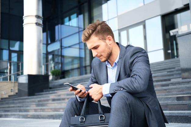 Przystojny mężczyzna wykonawczy siedzi na schodach na zewnątrz budynku.