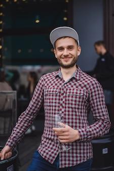 Przystojny mężczyzna wytatuowany na tarasie letnim w kawiarni w mieście pije wino. street cafe.