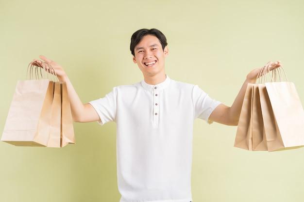 Przystojny mężczyzna z azji trzyma w ręku papierowe torby