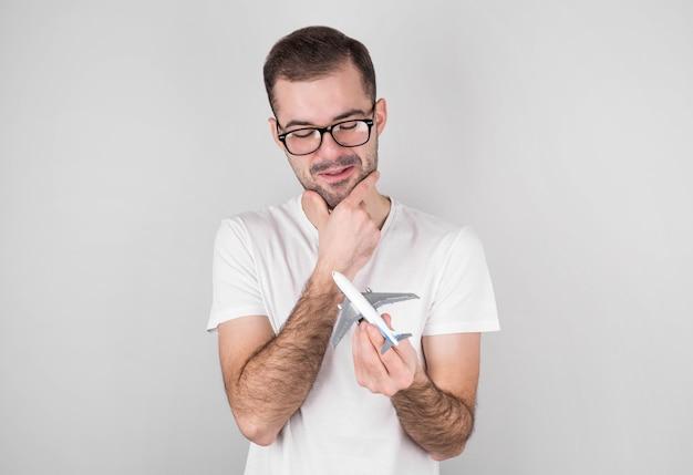 Przystojny mężczyzna z białą koszulką, trzymając samolocik na szarym tle