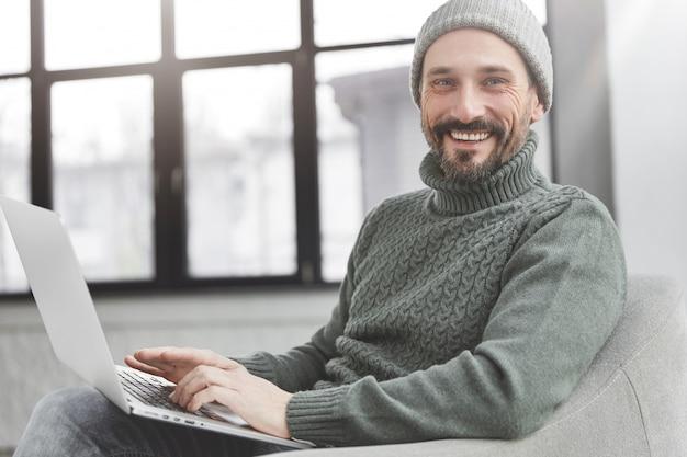Przystojny mężczyzna z brodą i laptopem