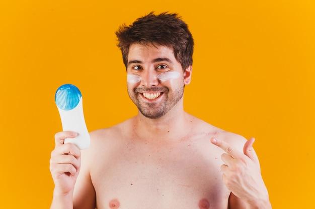 Przystojny mężczyzna z brodą na wakacjach w strojach kąpielowych, trzymając butelkę balsamu przeciwsłonecznego