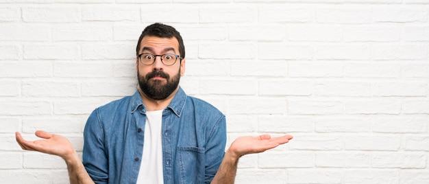 Przystojny mężczyzna z brodą nad białym murem, mając wątpliwości, podnosząc ręce