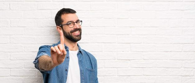 Przystojny mężczyzna z brodą nad białym murem pokazując i podnosząc palec