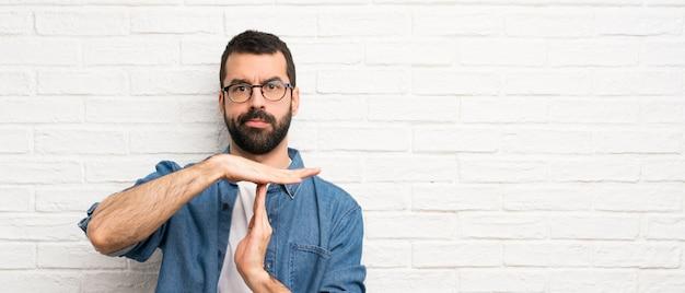 Przystojny mężczyzna z brodą nad białym ściana z cegieł robi czasowi out gestykuluje