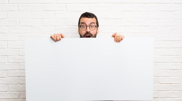 Przystojny mężczyzna z brodą nad białym ściana z cegieł trzyma pustego plakat