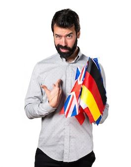 Przystojny mężczyzna z brodą trzyma wiele flag i podejmowania niespodzianek gest