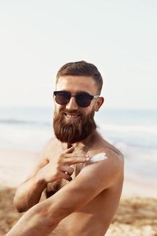 Przystojny mężczyzna z brodą, w okularach przeciwsłonecznych do opalania z balsamem do ciała w lecie. męski model fitness opalanie przy użyciu kremu słonecznego dla zdrowej opalenizny.