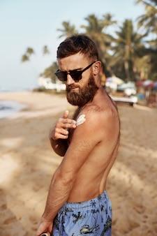 Przystojny mężczyzna z brodą, w okularach przeciwsłonecznych do opalania z balsamem do ciała w lecie.