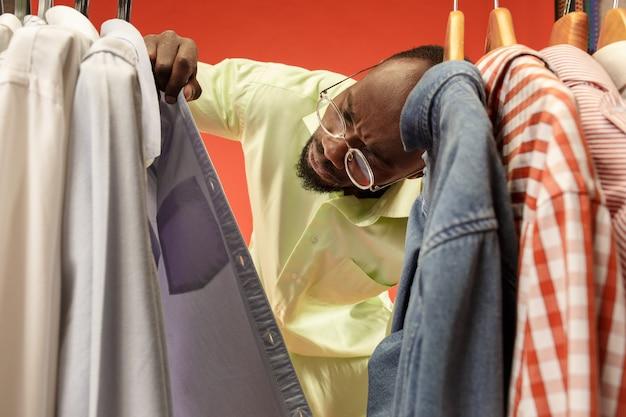 Przystojny mężczyzna z brodą wybiera koszulę w sklepie