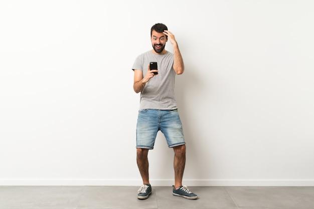 Przystojny mężczyzna z brodą zaskoczony i wysyłanie wiadomości