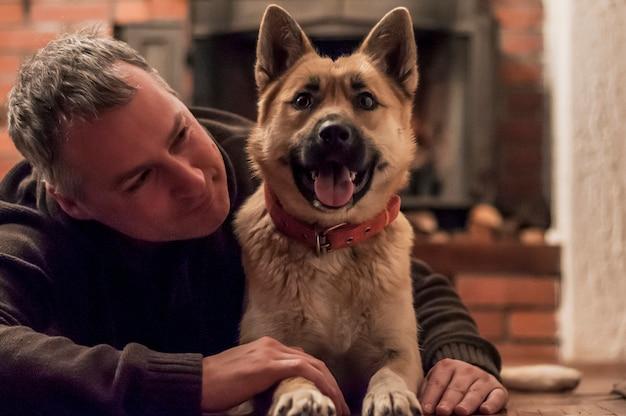 Przystojny mężczyzna z cute psa w domu. atrakcyjny mężczyzna leży na podłodze z psem w domu w salonie. pozytywne ludzkie emocje, wyraz twarzy, uczucia.