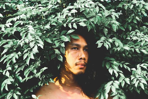 Przystojny mężczyzna z długą fryzurą pozuje z rośliną. styl filtrów w stylu vintage i filmie