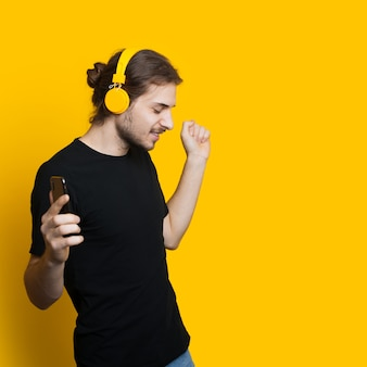 Przystojny mężczyzna z długimi włosami i brodą słucha muzyki przez słuchawki, pozując w pobliżu żółtego