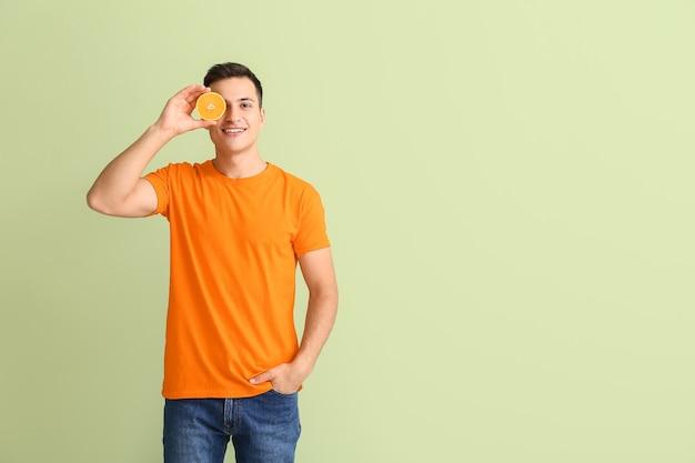 Przystojny mężczyzna z dojrzałą pomarańczą na kolorowym tle