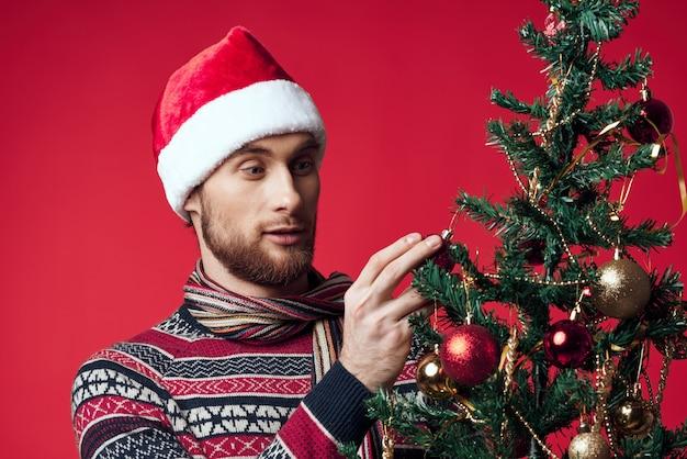 Przystojny mężczyzna z drzewem w jego rękach ozdoby wakacje zabawa czerwonym tle. zdjęcie wysokiej jakości