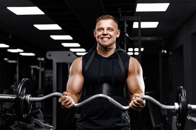 Przystojny mężczyzna z dużymi mięśniami, pozowanie na kamery na siłowni