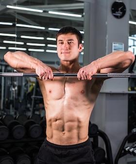 Przystojny mężczyzna z dużymi mięśniami, pozowanie na siłowni