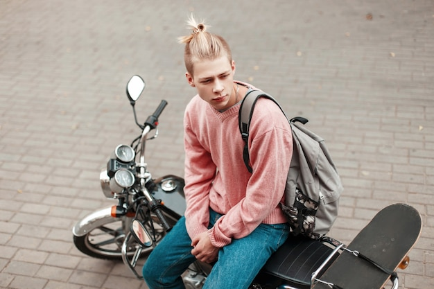 Przystojny mężczyzna z fryzurą w różowym swetrze z deskorolką i plecakiem siedzi na motocyklu