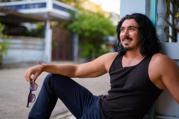 Przystojny mężczyzna z kręconymi włosami i wąsami na zewnątrz ulic