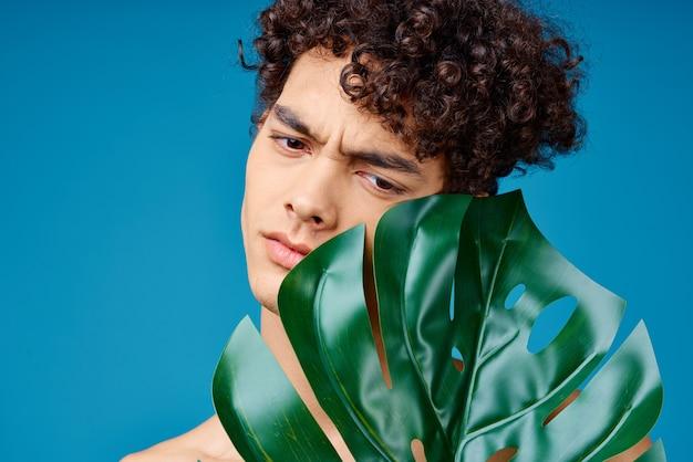 Przystojny mężczyzna z kręconymi włosami nagie ramiona zielone