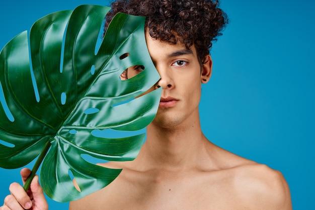 Przystojny mężczyzna z kręconymi włosami nagimi ramionami zielony liść