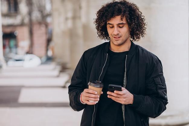Przystojny mężczyzna z kręconymi włosami pije kawę na ulicy