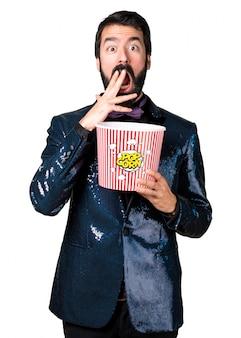 Przystojny mężczyzna z kurtka cekinowa jedzenie popcorns