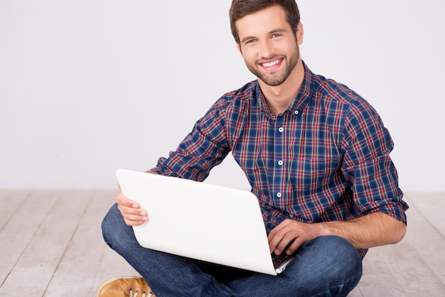 Przystojny mężczyzna z laptopem. wesoły młody człowiek pracuje na laptopie i uśmiecha się do kamery siedząc na drewnianej podłodze