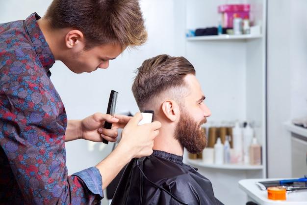Przystojny mężczyzna z moda podświetlone włosy na sobie białą koszulę robi fryzurę dla człowieka z brązowymi włosami w fryzjera.