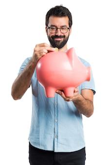 Przystojny mężczyzna z niebieskimi okularami gospodarstwa piggybank