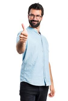 Przystojny mężczyzna z niebieskimi okularami z kciukiem do góry