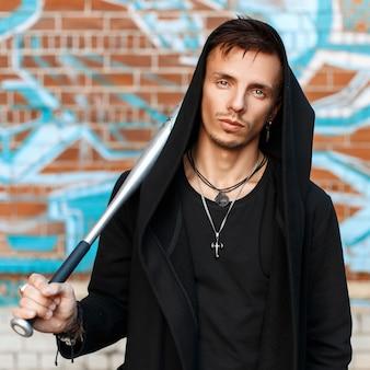 Przystojny mężczyzna z nietoperzem w czarnych ubraniach w kapturze w pobliżu ściany z cegły z graffiti